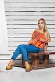 Beautiful blonde woman posing in studio. Sitting, wearing t-shirt and jeans royalty free stock photo