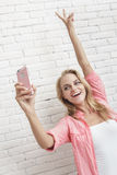 Beautiful blonde woman posing while taking photo with mobilephon. Portrait of beautiful blonde woman posing while taking photo with mobilephone camera Stock Image