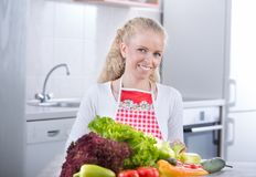 Woman with bunch of vegetables on table. Beautiful blonde woman preparing fresh vegetables for meal. Healthy food concept Royalty Free Stock Photography
