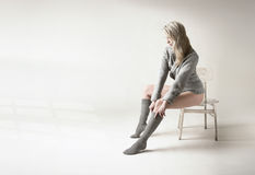 Beautiful blonde woman pulls her gray socks up. Young lady sits in white, clean room, and dresses up Stock Photos
