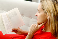 Beautiful blonde woman reads a book in the sofa Stock Images