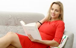 Beautiful blonde woman reads a book in the sofa Stock Photo