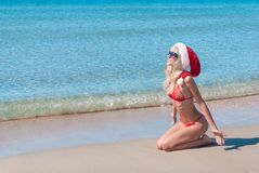 Beautiful blonde woman in red christmas hat and bikini on sea beach Stock Photography
