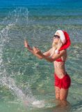 Beautiful blonde woman in red christmas hat on sea beach Royalty Free Stock Image
