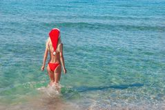 Beautiful blonde woman in red christmas hat on sea beach. Royalty Free Stock Image