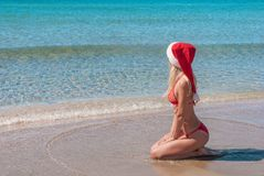 Beautiful blonde woman in red christmas hat on sea beach. Stock Photos