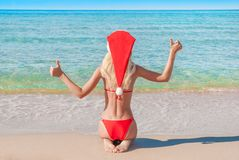 Beautiful blonde woman in red christmas hat on sea beach. Stock Photo