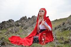 Beautiful blonde woman with red cloak sitting on a rock on the e Royalty Free Stock Photography