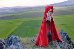 Beautiful blonde woman with red cloak standing barefoot in the w. Ind on the edge of a mountain in the sunset light. Loneliness. Silence. Soothing landscape stock images