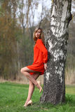 Beautiful blonde woman in red dress. Young woman with long legs standing in a park in spring time royalty free stock image