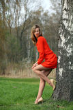 Beautiful blonde woman in red dress. Young woman with long legs standing in a park in spring time stock photo