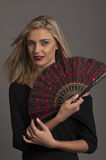 Beautiful blonde woman with red oriental fan Royalty Free Stock Images