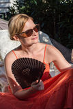 Beautiful blonde woman is relaxing in a hammock in the sun Royalty Free Stock Images