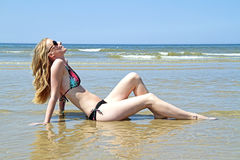 Beautiful blonde woman relaxing at the waterfront Royalty Free Stock Image
