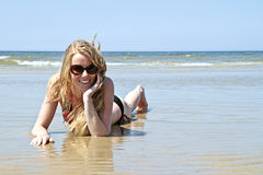 Beautiful blonde woman relaxing at the waterfront Royalty Free Stock Photography
