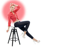 Beautiful blonde woman in retro style sitting on stool Royalty Free Stock Photography