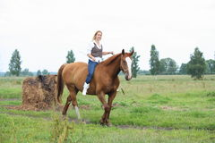 Beautiful blonde woman riding horse bareback. And without bridle Stock Photo