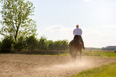 Beautiful blonde woman riding a horse in countryside Stock Photo