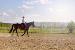 Beautiful blonde woman riding a horse in countryside Royalty Free Stock Photos