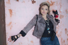 Beautiful blonde woman in rock style at the wall Stock Images
