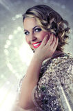 Beautiful blonde woman with short curly hair and shining glittery background. Stock Photos