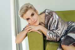 Beautiful blonde woman with short hair sitting. On green sofa. Perfect female face Stock Image