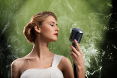 Beautiful blonde woman singer with a microphone Stock Photography