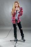 A beautiful blonde woman singing in microphone Royalty Free Stock Photos