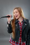 A beautiful blonde woman singing in microphone Stock Images