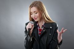 A beautiful blonde woman singing in microphone Royalty Free Stock Photo