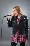 A beautiful blonde woman singing in microphone Stock Photos