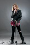 A beautiful blonde woman singing in microphone Royalty Free Stock Images