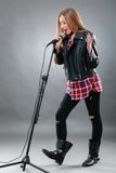 A beautiful blonde woman singing in microphone Stock Image