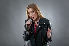 A beautiful blonde woman singing in microphone Royalty Free Stock Image