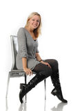 Beautiful blonde woman sit on chair. Portrait of a beautiful blonde woman with long hair and a smile sit on a chair of white background Royalty Free Stock Photos