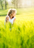 Beautiful blonde woman sits in the middle of a field Royalty Free Stock Images