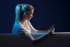 Beautiful blonde woman sits on sofa, and use her cellphone Stock Image