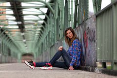 Beautiful blonde woman sitting on a bridge with graffiti. Girl with long legs in blue jeans and sneakers sitting on a bridge stock photos
