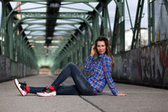 Beautiful blonde woman sitting on a bridge with graffiti. Girl with long legs in blue jeans and sneakers sitting on a bridge Stock Image