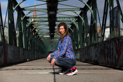 Beautiful blonde woman sitting on a bridge with graffiti. Girl with long legs in blue jeans and sneakers sitting on a bridge royalty free stock photography