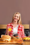 Beautiful Blonde Woman Sitting In Cafe Hold Orange Juice Order Beef Burger Served In Paper On Wooden Table Royalty Free Stock Photos