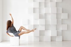 Beautiful blonde woman, sitting on a chair. Royalty Free Stock Photos