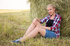 Beautiful blonde woman sitting in field with haystacks Royalty Free Stock Images