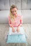 Beautiful blonde woman sitting on the floor using laptop Royalty Free Stock Photos