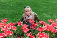 Beautiful blonde woman sitting on grass against landscape with red tulips stock image