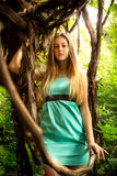 Beautiful blonde woman sitting on liana at rain forest Stock Images