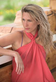 Beautiful blonde woman is sitting and looking at s. Young beautiful woman sits on wooden bench Stock Image