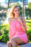 Beautiful Blonde Woman Sitting In The Park Stock Image