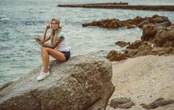 Beautiful blonde woman sitting on a rock by the sea and listening to music on stylish headphones on the tablet. hands. With a tattoo. The style of summer stock image