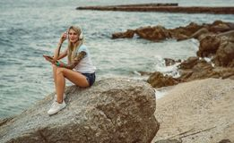 Beautiful blonde woman sitting on a rock by the sea and listening to music on stylish headphones on the tablet. hands. With a tattoo. The style of summer stock images